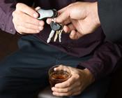 photo: man holding a drink handing over car keys